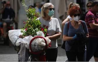 Una donna anziana con la mascherina porta a mano una bicicletta