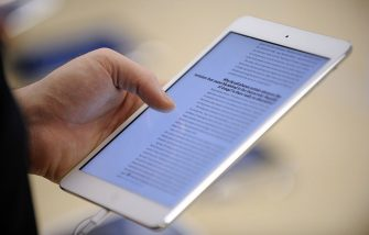 A man reads on a new iPad mini during the opening of a new Apple store on November 15, 2012 in Saint-Herblain, western France.    AFP PHOTO / JEAN-SEBASTIEN EVRARD        (Photo credit should read JEAN-SEBASTIEN EVRARD/AFP via Getty Images)