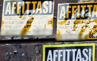 Cartelli di affittasi affissi su un muro di una città