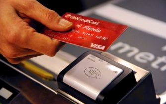 Una persona usa il bancomat per pagare ai tornelli della metropolitana