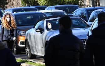 Una donna con il volto coperto da una mascherina sanitaria cammina accanto a auto in coda in una via del centro, Milano, 26 gennaio 2021. Nonostante il lungo periodo di lockdown, l'aria della Lombardia non è migliorata. Per il terzo anno consecutivo, nel 2020 la Lombardia ha rispettato i limiti per quanto riguarda il Pm10, anche se c'è stato un leggero e inaspettato peggioramento della media annua e un aumento dei giorni di superamento del limite. ANSA/DANIEL DAL ZENNAROANSA/DANIEL DAL ZENNARO