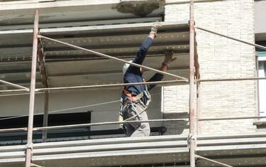 Un operaio edile sui ponteggi di un palazzo in ristrutturazione, in una immagine del 18 aprile 2017. ANSA/LUCA ZENNARO
