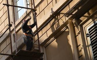 Un operaio edile su ponteggi intento a montare la ponteggiatura in un palazzo in ristrutturazione, Genova, 12 aprile 2017. ANSA/LUCA ZENNARO