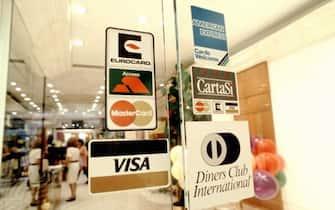 I loghi di diverse compagnie bancarie sulla porta di un negozio