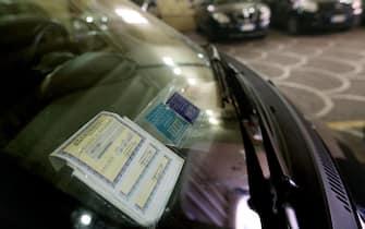 Il contrassegno di carta, ricevuta dell'assicurazione auto, sul parabrezza di una vettura. ANSA/ALESSANDRO DI MEO