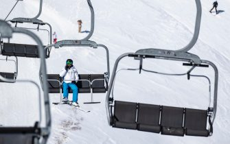 epa09051647 A man takes a ski lift of Palandoken mountain during the coronavirus pandemic (COVID-19) in Erzurum, Turkey, 04 March 2021. Winter tourism began in Palandoken, Turkey's largest ski center in the East, 01 December 2020. With the Turkish government eases COVID-19 pandemic restrictions, ski facilities started to fill up step by step. Since there was no Covid-19 test requirement at the entrance to the country, mostly Russian and Asian tourists are interested in these kind of tourist centers in Turkey.  EPA/ERDEM SAHIN