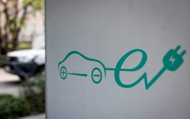 A signage for electric vehicle charging station is pictured at a parking area in Bangkok on March 30, 2021. (Photo by Jack TAYLOR / AFP) (Photo by JACK TAYLOR/AFP via Getty Images)