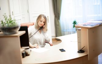 Young female receptionist talking on phone in office