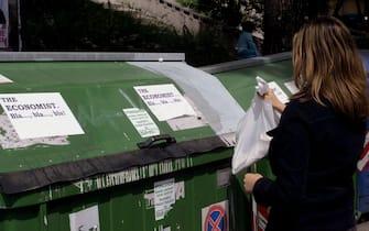 Una signora mentre getta la spazzattura in un bidone