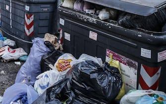 Un bidone della spazzatura con dei sacchi per strada