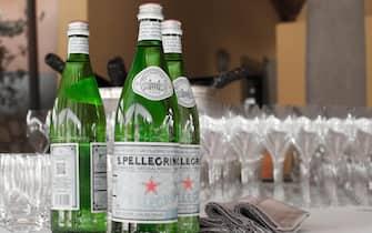 Tavola a buffet imbandita con bottiglie d'acqua San Pellegrino, bicchieri e tovaglioli