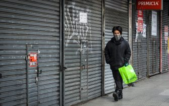 BUENOS AIRES, ARGENTINA - JULY 02:  A man wearing a scarf on his face walks in front of closed shops at Once neighborhood on July 2, 2020 in Buenos Aires, Argentina. According to the national statistics bureau (INDEC), economy in Argentina shrank 26% year on year in April, the first full month of coronavirus lockdown. Due to increasing number of cases in Buenos Aires Aires and its metropolitan area, authorities tightened restrictions allowing only essential shops and industries to remain open to public. Apart from dealing with the pandemic, Argentina is on default and holds a negotiation with creditors to restructure a 66 billion USD debt. (Photo by Marcelo Endelli/Getty Images)