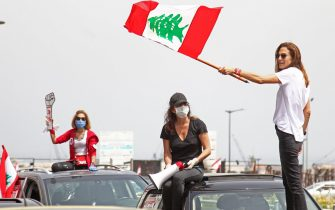 Dozens of Lebanese protesters defy a stay-at-home order to protest in their cars deteriorating living conditions and maintain pressure on a political elite under fire since mass protests erupted last October, in the capital Beirut on April 21, 2020. - Lebanon's parliament met today in a conference hall to allow for social distancing between lawmakers amid the coronavirus pandemic, while outside anti-government protesters demonstrated in a car convoy.Outside the venue, dozens of protesters drove a noisy convoy of cars covered in slogans, drivers honking their horns and passengers brandishing the national flag and leaning out of the windows in face masks. (Photo by IBRAHIM  AMRO / AFP)