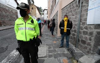 epa09128697 A police agent stands on duty outside a polling station in Quito, Ecuador, on 11 April 2021. Ecuadorians are choosing the next president in a runoff election.  EPA/JOSE JACOME
