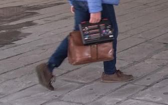 Un uomo cammina con una valigetta da lavoro