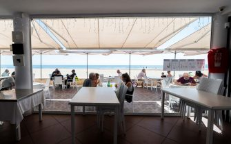 People enjoy the sunny weather at a terrace in La Malvarrosa beach in Valencia, on May 19, 2020, as some Spanish provinces are allowed to ease lockdown restrictions amid the coronavirus (COVID-19) outbreak. - Spain began last week a three-phase plan to end lockdowns for half the country by the end of June. (Photo by JOSE JORDAN / AFP)
