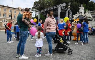 Una famiglia assiste alla manifestazione #NO1luglio per la riapertura dei parchi tematici e acquatici a Piazza del Popolo, Roma, 11 maggio 2021. ANSA/RICCARDO ANTIMIANI