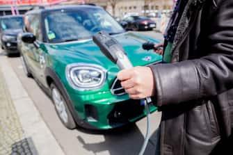 Un uomo ricarica l'auto elettrica di sua proprietà