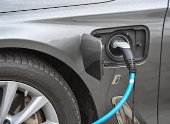 Un'auto elettrica mentre viene ricaricata a una colonnina