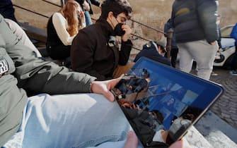 Napoli, giovani studenti liceali seguono lezione a distanza (DAD) per strada, causa diffusione del virus coronavirus COVID 19.
