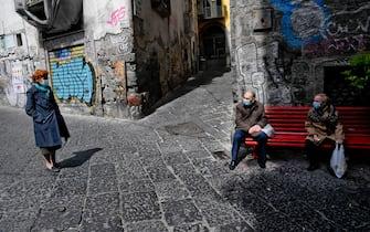 Anziani, indossando mascherine anti contagio,  si riposano su una panchina Rossa, simbolo della lotta alla Violenza sulle donne, nel centro antico di Napoli, 21  aprile   2021  ANSA/CIRO FUSCO