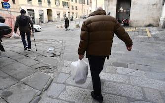 La distribuzione di generi alimentari organizzata dalla Comunita' di Sant'Egidio alla mensa di S.Sabina nel centro storico della citta'. I volontari gestiscono 10 punti in tutta Genova. Molti stranieri, ma anche anziani soli che non riescono ad arrivare a fine del mese con la pensione, e negli ultimi mesi anche famiglie italiane in difficolta' sia lavorative che economiche. Genova, 08 marzo 2021. ANSA/LUCA ZENNARO
