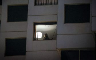 Australian resident Sara Medici, partner of the photographer, stands in the window of her hotel room during mandatory quarantine as a result of COVID-19 restrictions after arriving from Italy, in Sydney on September 25, 2020, in Australia. Sara Medici spent two weeks in mandatory hotel quarantine after her return from Italy to Australia. All international arrivals into Australia must go into mandatory 14-day hotel quarantine as part of Australia's strict border controls due to the ongoing COVID-19 pandemic.   (Photo by David Gray/Getty Images)