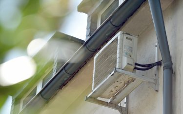 An air conditioning unit on the side of a residential building in Essen, Germany, 23 August 2017. Photo: Caroline Seidel/dpa (Photo by Caroline Seidel/picture alliance via Getty Images)