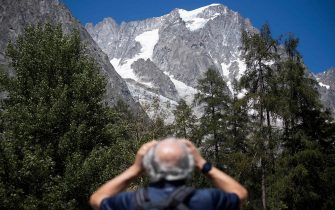 TOPSHOT - A man looks up to the Planpincieux glacier from the village of La Palud, in Courmayeur, Val Ferret, northwestern Italy, on August 6, 2020. - Several dozen people have been evacuated in northwestern Italy as a huge chunk of a glacier in the Mont Blanc massif threatens to break off due to high temperatures. (Photo by MARCO BERTORELLO / AFP)
