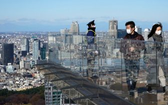 epa08889221 Visitors wearing face masks look at the city scape from an observation deck in Tokyo, Japan, 04 December 2020 (issued 17 December 2020). According to media reports, Tokyo recorded more than 800 infection of SARS-CoV-2 on 17 December, a record daily number.  EPA/FRANCK ROBICHON