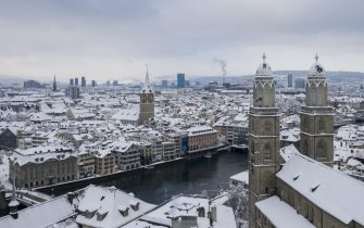 epa08939264 View of the snow-covered Grossmuenster church in Zurich, Switzerland, 15 January 2021. Record-breaking amounts of fresh snow have fallen in parts of Switzerland since Wednesday, with a massive impact on traffic.  EPA/ENNIO LEANZA