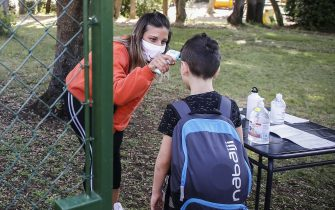 Un' educatrice della scuola per l'infanzia ''In Crescendo'' misura la temperatura con un termoscanne ad alcuni  bambini prima di farli accedere in un parco dove da oggi inizia il centro estivo, Roma 15 giugno 2020. ANSA/FABIO FRUSTACI