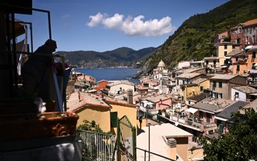 A man is silhouetted on his balcony in Vernazza, Cinque Terre National Park, near La Spezia, nortwestern Italy, on June 24, 2021. (Photo by MARCO BERTORELLO / AFP) (Photo by MARCO BERTORELLO/AFP via Getty Images)