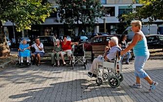 Una badante accompagna un anziano in un giardino pubblico