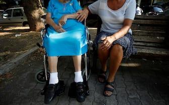 Una badante insieme all'anziana che ha in cura seduta su una panchina