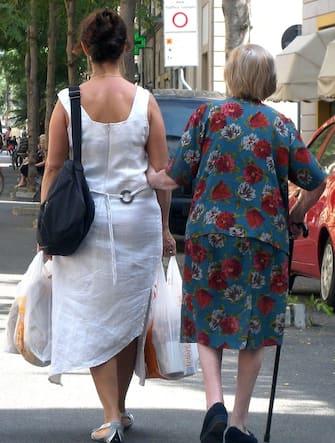 Una badante accompagna una signora anziana a far la spesa