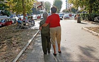 Una badante accompagna una signora anziana in una passeggiata