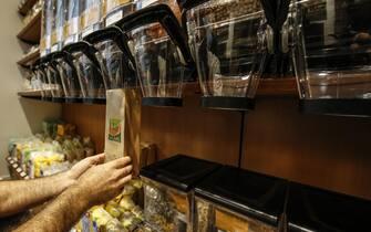 Un addetto alla vendita riempie un sacchetto da un distributore di cereali e legumi secchi in un negozio di prodotti bio, Roma, 18 ottobre 2019.  ANSA / FABIO FRUSTACI