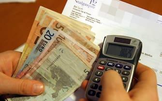 Una bolletta con una calcolatrice e alcune banconote