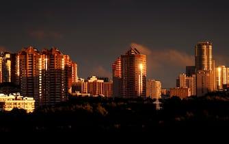 epa09445820 Buildings illuminated in orange during sunset  in Moscow, Russia, 03 September 2021.  EPA/YURI KOCHETKOV