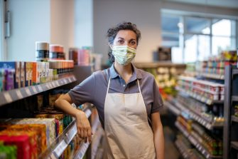 Portrait of a woman working in supermarket wearing a face mask looking at camera. Store assistance with face mask and apron leaning to a rack in grocery store.