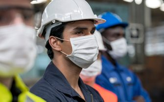 Shot of Multi-ethnic in heavy industry workers wearing face mask, helmet and jumpsuit. Focus on maintenance engineer.