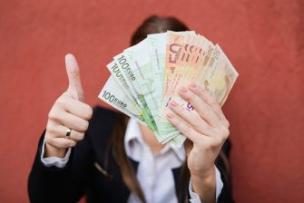 Woman holding bunch of euros as a result of financial , government aid or loan approved