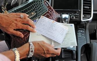 Un bollo e un libretto di circolazione di un'automobile di lusso, fotografati oggi 16 luglio 2011 a Pisa.ANSA/FRANCO SILVI