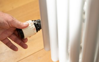 14 October 2021, Baden-Wuerttemberg, Stuttgart: A hand regulates a thermostat on a heater in an apartment. Due to rising energy prices, heating costs are becoming more expensive. Photo: Bernd Weißbrod/dpa (Photo by Bernd Weißbrod/picture alliance via Getty Images)