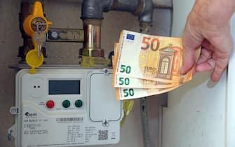 Milano - Aumento del costo della bolletta del gas e dell'energia elettrica  - soldi euro e contatore della luce