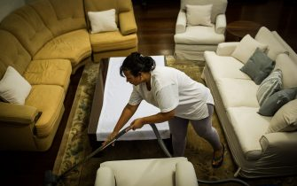 Brazilian Cassia Mendes, who has been working as a housekeeper for more than 20 years, cleans a house in Sao Paulo, Brazil on Februrary 19, 2012. Brazil enacted on April 2, 2013 a constitutional amendment to grant domestic workers health insurance and other benefits enjoyed by other workers. In this huge South American country, 6.1 million women are domestic helpers, representing about 15 percent of the country's female labor force, according to a 2011 survey by the country's National Statistics Bureau IBGE. AFP PHOTO/Yasuyoshi CHIBA        (Photo credit should read YASUYOSHI CHIBA/AFP via Getty Images)