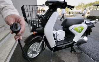 """An engineer (L) for Japan's Honda Motor demonstrations how to charge the company's prototype model of a new electric motorcycle called the """"EV-neo"""" at the company's research and development center in Wako, suburban Tokyo on April 13, 2010. The """"EV-neo"""", equipped with Toshiba-made Li-ion batteries, can travel more than 30 kms with a full-charge and be recharged to 80 percent in 20 minutes. Honda will start a leasing service at the end of this year.   AFP PHOTO / Yoshikazu TSUNO (Photo credit should read YOSHIKAZU TSUNO/AFP via Getty Images)"""