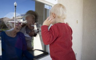 VENTURA, CA - APRIL 3: Mary-Lou McCullagh, 83, and her husband Bob, 84, greet Axel Stirton, 2, the little boy who lives across the street April 3, 2020 in Ventura, California. Mary-Lou and Bob are in isolation from the Covid-19 pandemic, trying to ensure that they do not come in contact with the virus. Mary-Lou has a medical condition that makes her especially vulnerable. They are using Zoom technology to stay in touch with family and friends. Axel is a regular visitor in normal times, but he can no longer come into the house because of the risks of the Covid-19 virus. Mary-Lou and Bob comfort him in his confusion through the window. Mary-Lou is wearing Happy Birthday glasses in honor of her sons birthday which was yesterday. As infection rates soar in the USA, more and more elderly people are in isolation and cut off from any physical contact with their families and friends. (Photo by Brent Stirton/Getty Images)