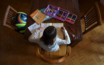 TOPSHOT - A girl does her school work at a table in a living room in a flat in Eichenau, southern Germany, on March 17, 2020, as schools across the country are closed due to the novel coronavirus. (Photo by Christof STACHE / AFP) (Photo by CHRISTOF STACHE/AFP via Getty Images)